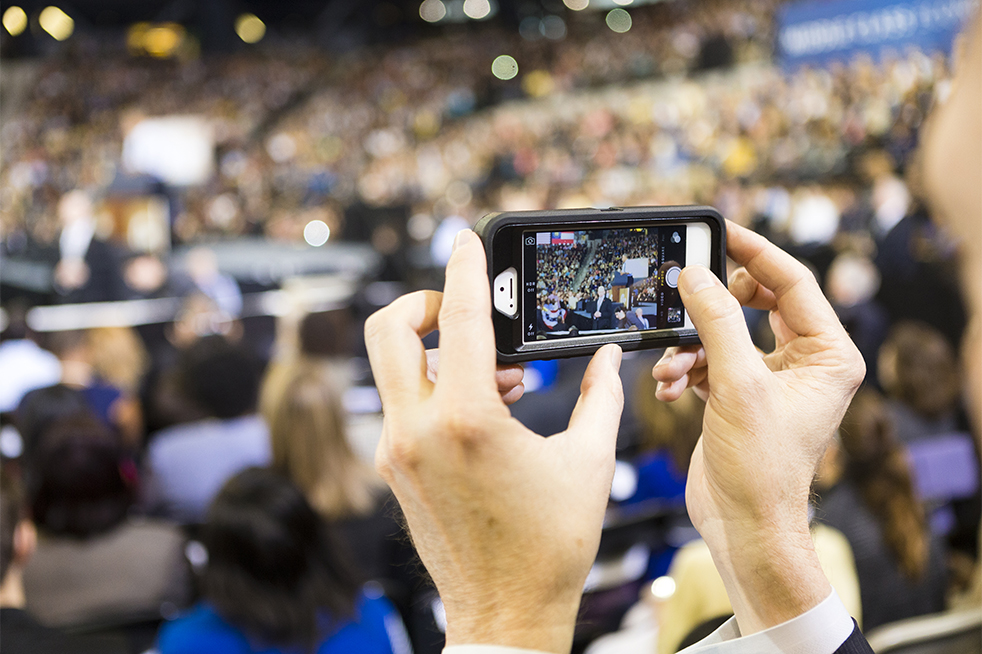 A student take a photo graph of the president on his cell phone during the address. // Photo by John Nakano